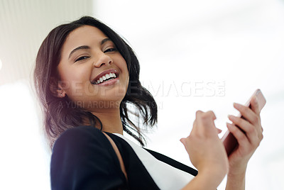 Buy stock photo Cropped portrait of an attractive young businesswoman smiling while using a smartphone in a modern office