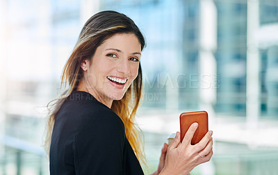 Buy stock photo Cropped portrait of an attractive young businesswoman holding her smartphone in her office