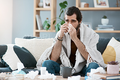 Buy stock photo Shot of a sickly young man blowing his nose with a tissue in his living room