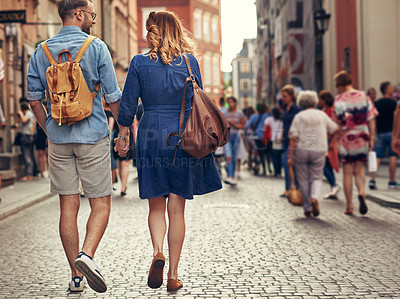 Buy stock photo Rearview shot of a couple walking through a foreign city