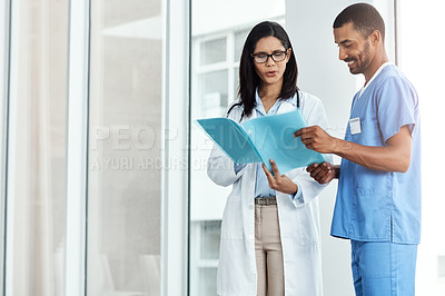 Buy stock photo Shot of two young doctors discussing the contents of a file in a modern hospital