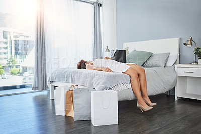 Buy stock photo Shot of a young woman sleeping on her bed with shopping bags around her