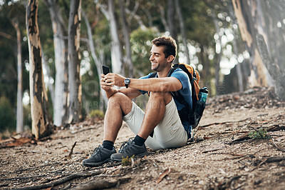 Buy stock photo Cropped shot of a carefree young man taking a quick break from hiking up a mountain during the day