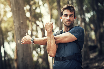 Buy stock photo Cropped shot of a handsome young man stretching before heading off on his hike in the mountains