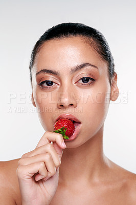 Buy stock photo Shot of a beautiful young woman eating a strawberry against a studio background