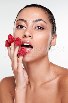 Buy stock photo Shot of a beautiful young woman eating raspberries off her fingers against a studio background