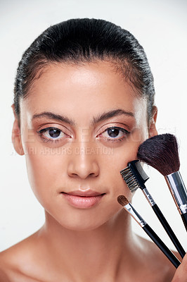 Buy stock photo Shot of a beautiful young woman with brushes next to her face against a studio background