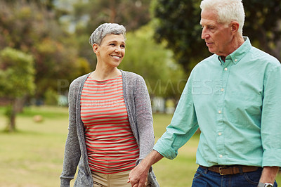 Buy stock photo Shot of an affectionate senior couple holding hands while walking through the park