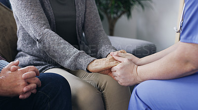 Buy stock photo Shot of a nurse holding hands with a senior woman while sitting next to her husband