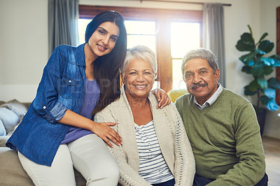 Buy stock photo Portrait of a beautiful senior couple posing with their daughter while sitting on a sofa together at home