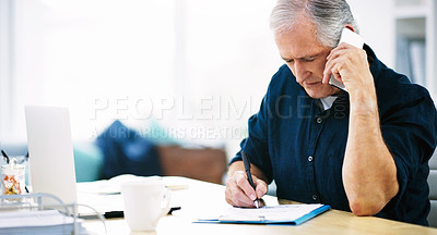 Buy stock photo Shot of a mature businessman writing a few notes down while answering a phone call in his office