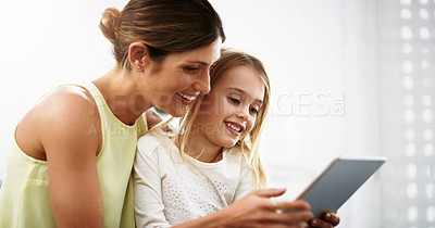 Buy stock photo Shot of a beautiful young mother and her daughter using a digital tablet together at home