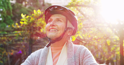 Buy stock photo Cropped shot of a cheerful elderly woman riding a bicycle outside in a park