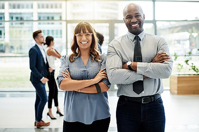 Buy stock photo Cropped portrait of two businesspeople standing with their arms crossed in the office with colleagues in the background