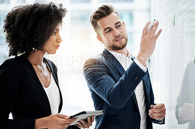 Buy stock photo Cropped shot of two young businesspeople strategizing on a whiteboard in their corporate office