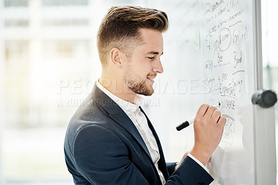Buy stock photo Cropped shot of a handsome young businessman strategizing on a whiteboard in his corporate office