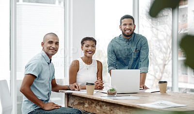 Buy stock photo Portrait of three young businesspeople sitting around a table and having a meeting at work