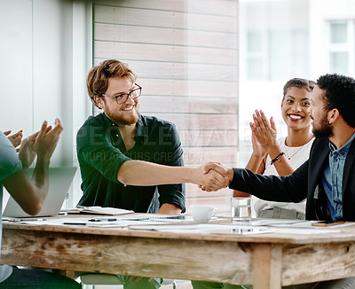 Buy stock photo Shot of two young businessmen shaking hands during a meeting in an office