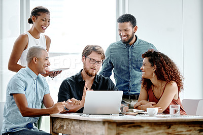 Buy stock photo Shot of a group of young businesspeople working on a laptop together in their office