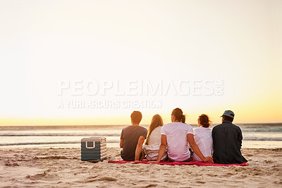 Buy stock photo Rearview shot of a group of friends watching the sunset on the beach