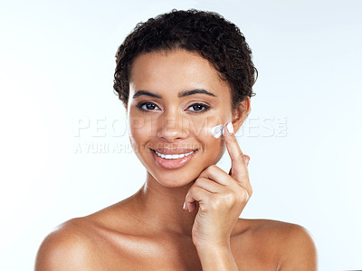 Buy stock photo Portrait of an attractive young woman posing while applying cream to her face  against a white background