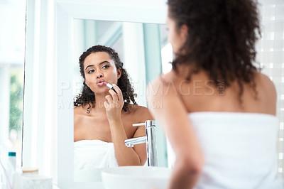 Buy stock photo Shot of a beautiful woman applying lipstick in her bathroom mirror