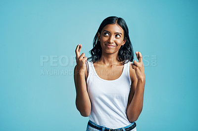 Buy stock photo Studio shot of a beautiful young woman crossing her fingers against a blue background