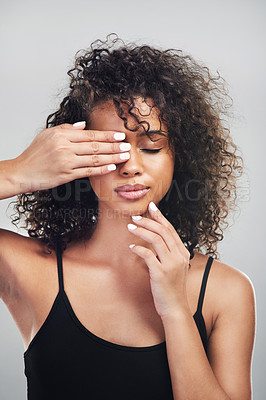 Buy stock photo Studio shot of a beautiful young woman posing with her hand over her eye