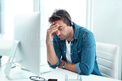 Buy stock photo Shot of a young male call centre agent suffering from a headache in his office