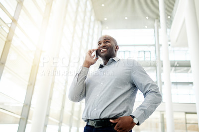 Buy stock photo Cropped shot of a confident young businessman talking on his cellphone at work during the day