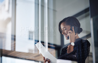 Buy stock photo Shot of an attractive young businesswoman using a smartphone and reading a document in a modern office