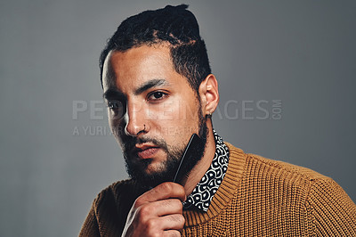Buy stock photo Studio portrait of a handsome young man combing his beard against a grey background
