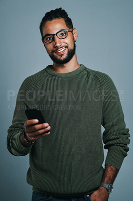 Buy stock photo Studio portrait of a handsome and stylish young man using a smartphone against a grey background