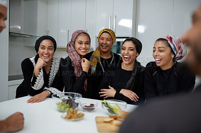 Buy stock photo Shot of a group of young muslim friends having a conversation together in the kitchen indoors