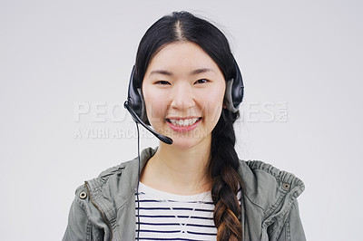 Buy stock photo Studio portrait of an attractive young female customer service representative wearing a headset against a grey background