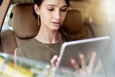 Buy stock photo Shot of a beautiful young businesswoman using a digital tablet while sitting in the backseat of a car