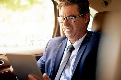Buy stock photo Shot of a mature businessman using a digital tablet while sitting in the backseat of a car