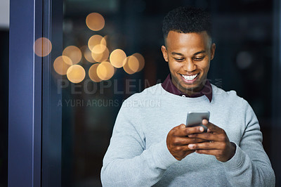 Buy stock photo Cropped shot of a cheerful young businessman texting on his cellphone inside the office during the night