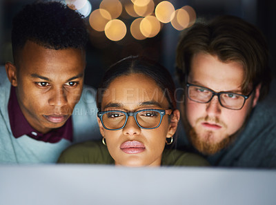 Buy stock photo Cropped shot of a cheerful young group of businesspeople working on a computer together in the office at night