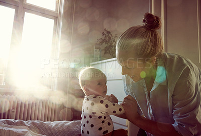 Buy stock photo Cropped shot of an affectionate young mother bonding with her adorable baby on a bed at home