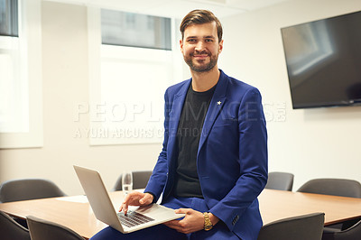 Buy stock photo Portrait of a handsome young businessman using a laptop in his office