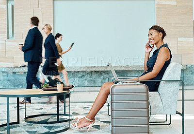 Buy stock photo Shot of a confident young businesswoman talking on her cellphone inside of a busy airport