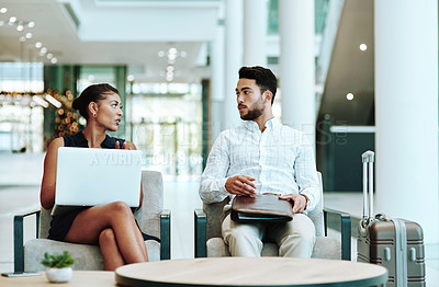 Buy stock photo Shot of  two young businesspeople having a discussion while waiting for their flight inside of an airport
