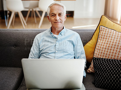 Buy stock photo Shot of a senior man relaxing and using a laptop on the sofa at home