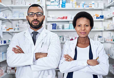 Buy stock photo Portrait of two confident young pharmacists standing with their arms folded inside of a pharmacy during the day