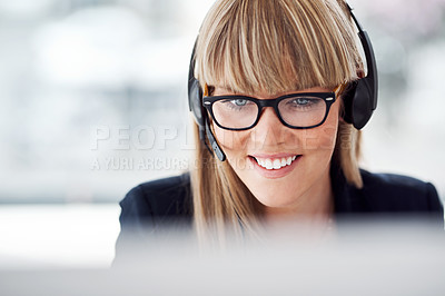 Buy stock photo Shot of an attractive young female customer service representative wearing a headset and working in her office