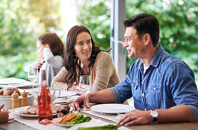 Buy stock photo Cropped shot of an affectionate young couple dining with their family for lunch outdoors