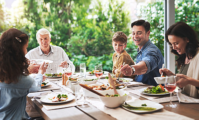 Buy stock photo Cropped shot of a happy father enjoying lunch with his family around a table outdoors