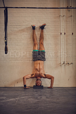 Buy stock photo Full length shot of a handsome young man doing handstands while working out in the gym