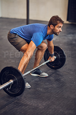 Buy stock photo High angle shot of a handsome young man lifting weights while working out in the gym